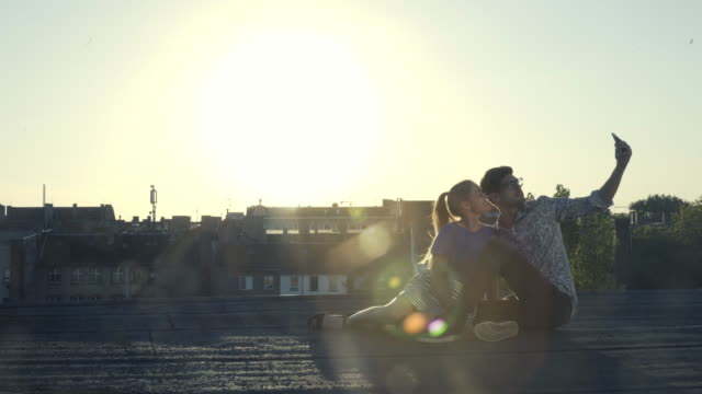 Young couple on a rooftop taking selfies