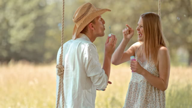 slo mo young couple on a swing blowing bubbles into each other - sleeveless dress stock videos and b-roll footage