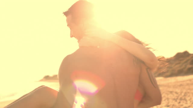 young couple on beach in sunset, man twirling woman round. - 30多歲 個影片檔及 b 捲影像