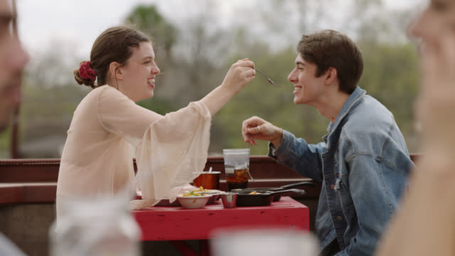 vídeos de stock, filmes e b-roll de young couple on lunch date share food and laugh on outdoor restaurant patio. - faqueiro