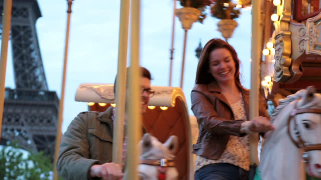 Young couple on Paris date ride horses on carousel with Eiffel Tower in background.