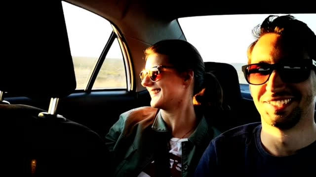 vidéos et rushes de jeunes couples en voyage sur la route avec un ami au volant hd vidéo - siège arrière de passager