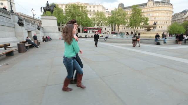 Young couple on romantic stroll through London walk down steps into Trafalgar Square.