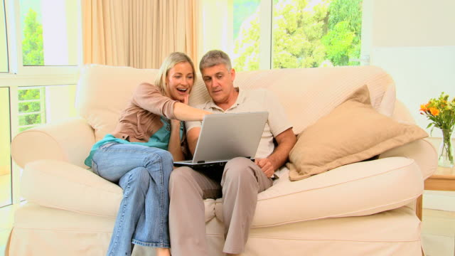 stockvideo's en b-roll-footage met young couple on sofa laughing over their laptop / cape town, western cape, south africa - tuindeur