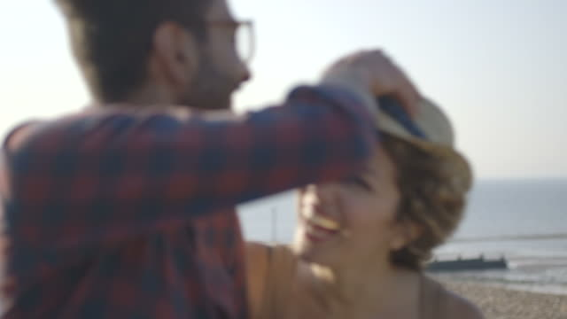 a young couple on the beach - abblenden stock-videos und b-roll-filmmaterial