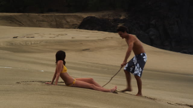 young couple on the beach - swimming shorts stock videos & royalty-free footage