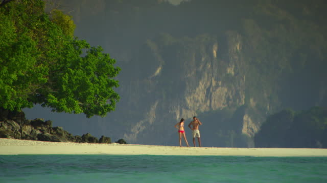 ws young couple on tropical beach, man talking on mobile phone, krabi, thailand - see other clips from this shoot 1459 stock videos and b-roll footage