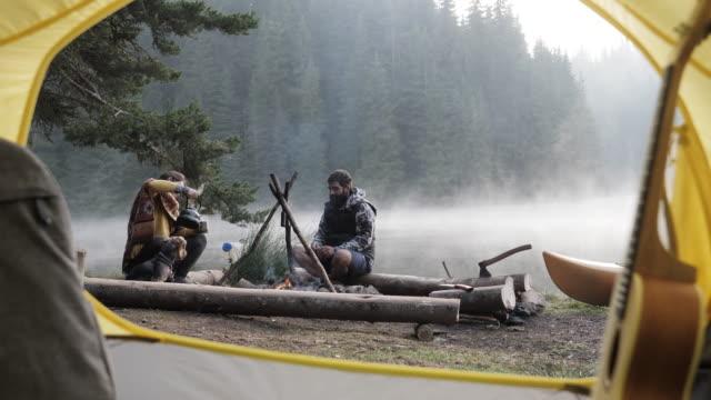 stockvideo's en b-roll-footage met jong paar op wilde het kamperen in aard. - wandelen buitensport