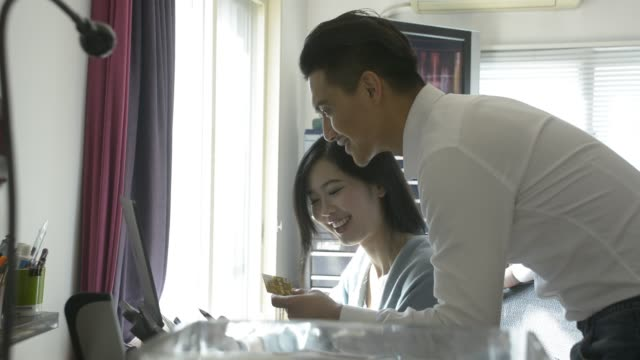 young couple online shopping with credit card at home