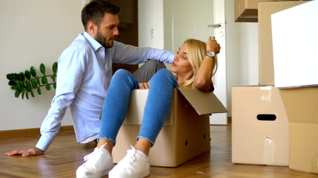 Young couple opening a box in new home