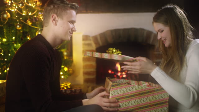 ds young couple opening christmas presents - fireplace stock videos & royalty-free footage