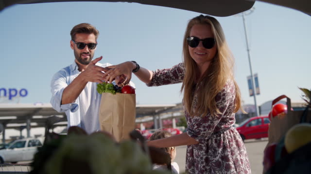 young couple packing groceries in car trunk - paper bag stock videos & royalty-free footage