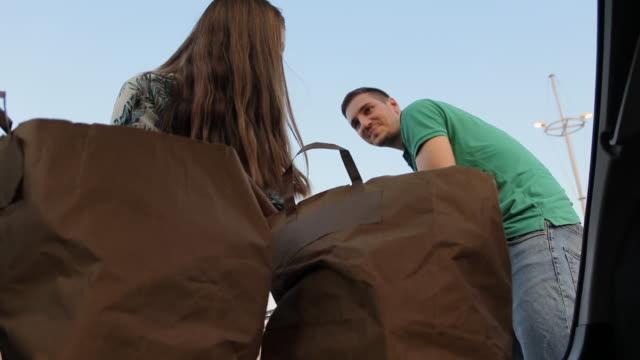 vidéos et rushes de jeunes couples d'emballage d'épicerie dans le coffre de voiture - aliments et boissons