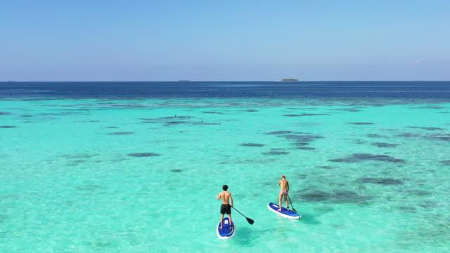 giovane coppia che pagaia su paddleboard - tourist video stock e b–roll