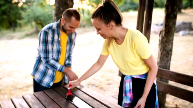 Young couple painting table in the park
