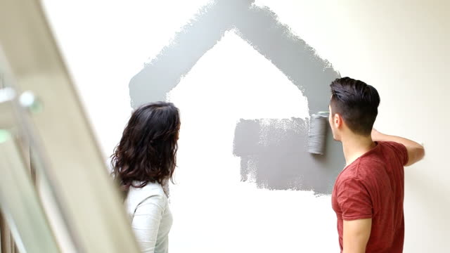 young couple painting wall in house shape - living room stock videos & royalty-free footage