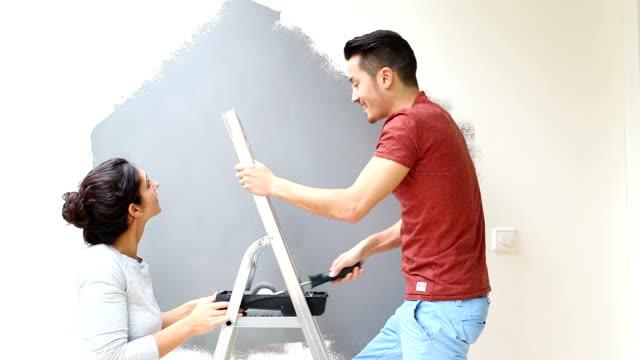 Coppia giovane con rullo pittura muro