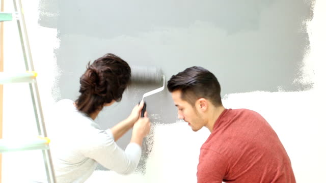 stockvideo's en b-roll-footage met young couple painting wall with paint roller - keukentrap