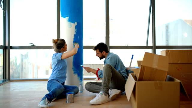 vídeos y material grabado en eventos de stock de joven pareja pintando muros. - reforma
