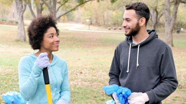 Young couple participate in a neighborhood cleanup project together