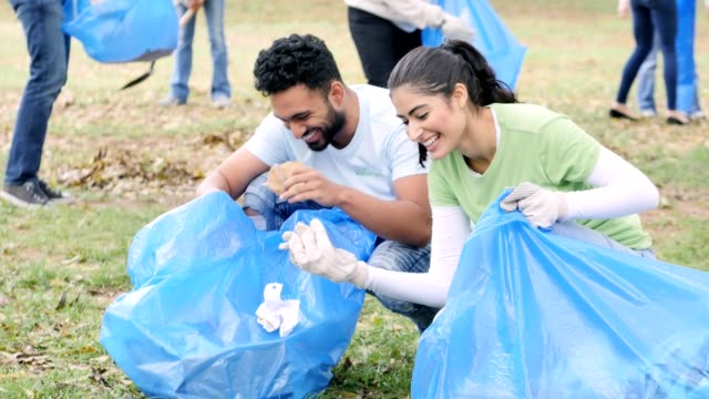 vídeos de stock e filmes b-roll de young couple participate in community cleanup day - sustainable resources