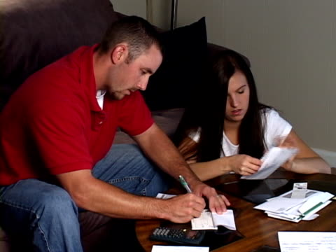 young couple paying bills - cheque financial item stock videos & royalty-free footage