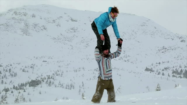 Young couple perform acrobatic feats in the snow