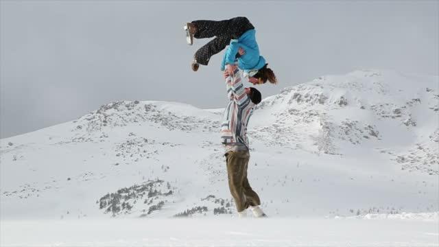 vidéos et rushes de jeune couple effectuer yoga acrobatique dans les montagnes - activité acrobatique