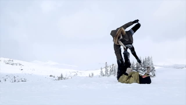stockvideo's en b-roll-footage met young couple perform acrobatic yoga in the mountains - acrobatiek