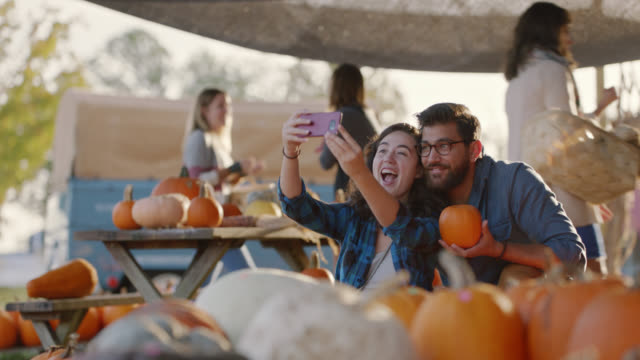 young couple pick out pumpkins together and take selfies at a farmers market - out take stock videos & royalty-free footage