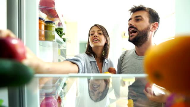 vidéos et rushes de jeune couple ramasser quelques fruits et légumes dans le réfrigérateur. - réfrigérateur