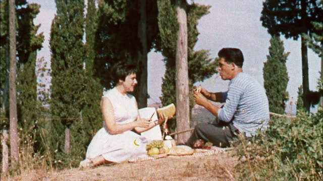 a young couple picnics on the shores of a mountain lake in the italian alps in italy. - 1950 1959 stock videos and b-roll footage