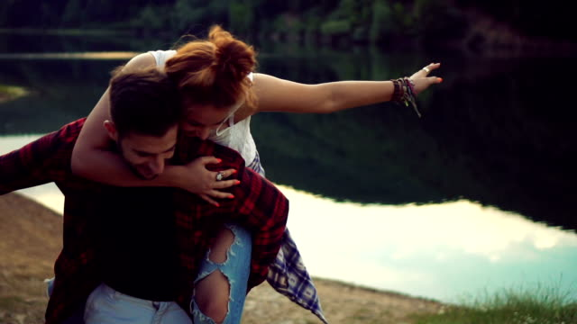 Young couple piggybacking on the lake
