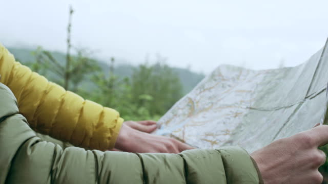 Young couple planning their trip with map. Close up on hands