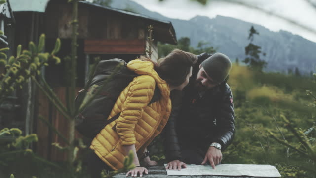 young couple planning their trip with map - capanna di legno video stock e b–roll