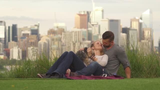 年輕夫婦玩狗在城市公園, 地平線後面 - 異性情侶 個影片檔及 b 捲影像