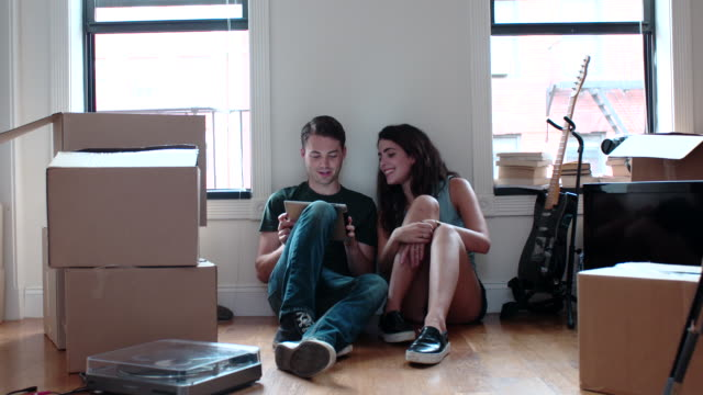 young couple play with tablet in boxed up apartment - couple relationship video stock e b–roll