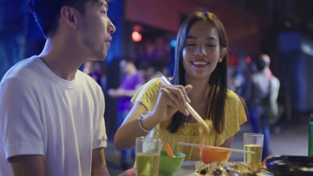 young couple playfully eating street food - ethnicity stock videos & royalty-free footage