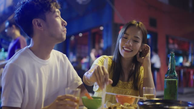young couple playfully eating street food - evening meal stock videos & royalty-free footage