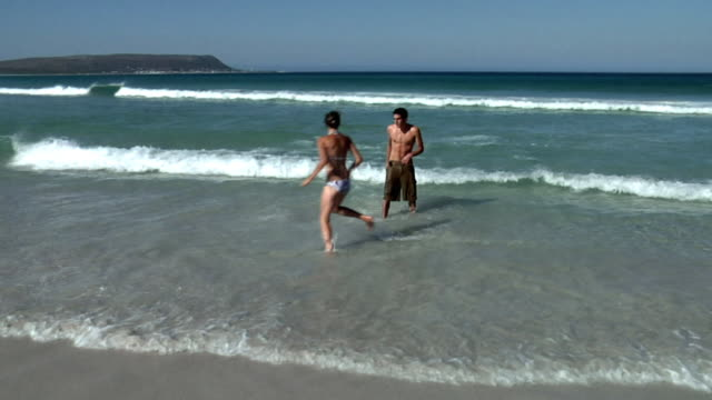 slo mo ws ha young couple playing and kissing in waves on beach, cape town, south africa - 16歳から17歳点の映像素材/bロール