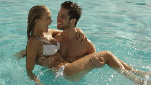 stockvideo's en b-roll-footage met young couple playing and laughing in pool - driekwartlengte