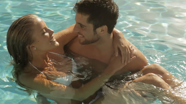 vídeos de stock, filmes e b-roll de young couple playing and laughing in pool - plano americano