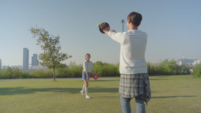 Young couple playing catch in the Han River Park