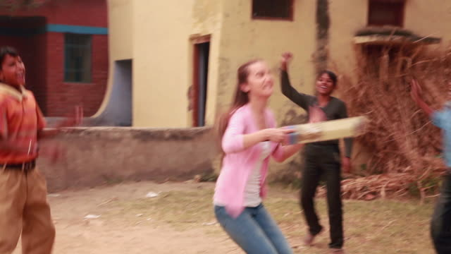 Young couple playing cricket match with rural kids, Faridabad, Haryana, India