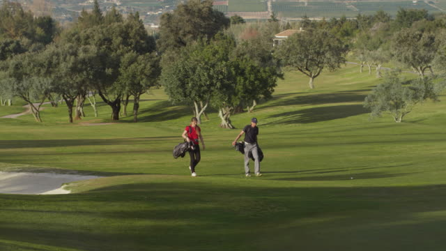 LS young couple playing golf on fairway, man plays ball, RED R3D 4K