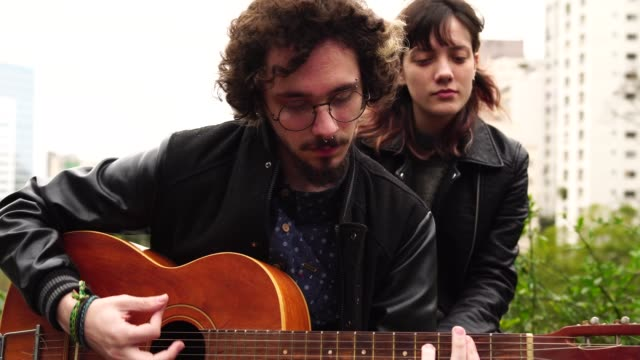 young couple playing guitar at city - music style stock videos and b-roll footage