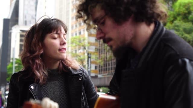 Junges paar spielt Gitarre bei City