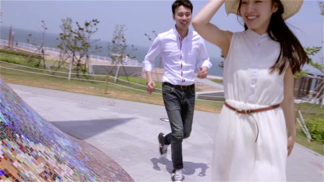vídeos de stock, filmes e b-roll de young couple playing tag in a park - brincadeira de pegar