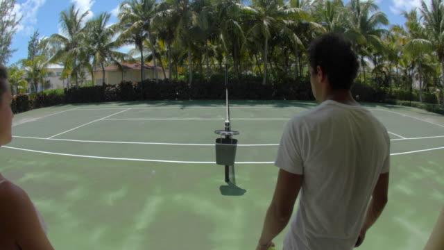 vídeos y material grabado en eventos de stock de a young couple playing tennis together on a tropical island. - pistas