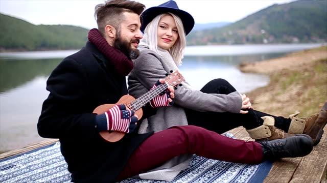 Young couple playing ukulele outdoors